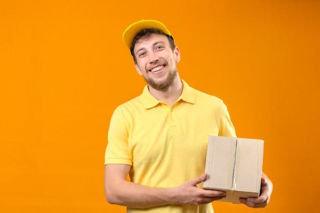 Bezorger in geel poloshirt en pet bedrijf doos pakket glimlachend vrolijk kijken camera staande op oranje