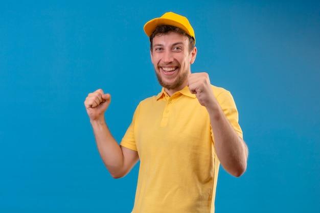 Bezorger in geel poloshirt en pet kijkt opgewonden verheugd over zijn succes en overwinning zijn vuisten balancerend van vreugde blij om zijn doel en doelen te bereiken staande op geïsoleerd blauw
