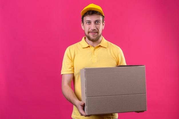 Bezorger in geel poloshirt en pet met grote kartonnen doos op zoek zelfverzekerd glimlachend vriendelijk met blij gezicht staande op geïsoleerde roze