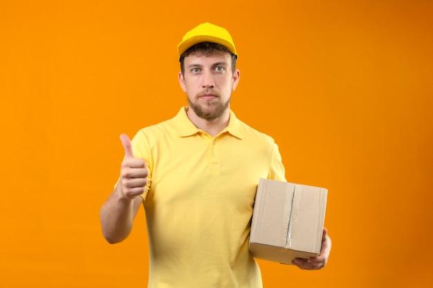 Bezorger in geel poloshirt en pet met kartonnen doos op zoek zelfverzekerd met duim omhoog staande op oranje