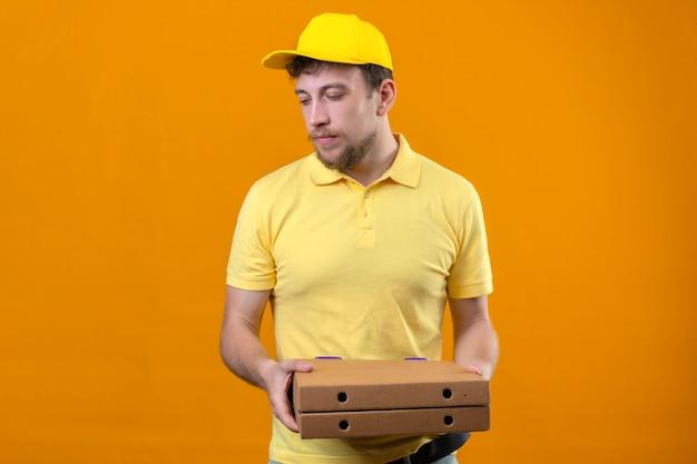 Bezorger in geel poloshirt en pet met pizzadozen opzij kijken met een ongelukkig gezicht staande op oranje
