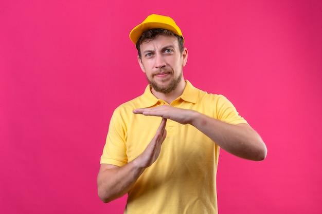 Bezorger in geel poloshirt en pet op zoek verveeld maken time-out gebaar op roze