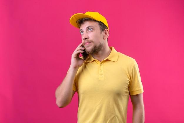 Bezorger in geel poloshirt en pet praten op mobiele telefoon opzoeken staande met dromerige blik op geïsoleerde roze