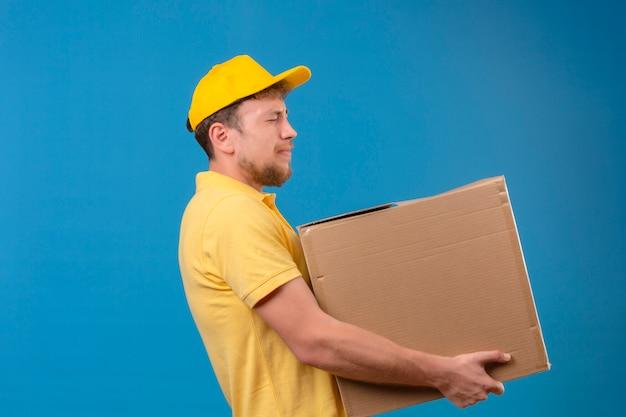 Bezorger in geel poloshirt en pet staat met grote kartonnen doos die lijdt aan zwaar gewicht op blauw