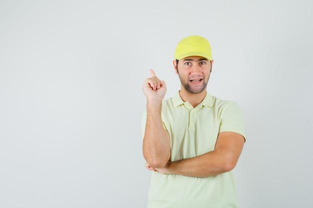 Bezorger in geel uniform die omhoog wijst en er zelfverzekerd uitziet, vooraanzicht.