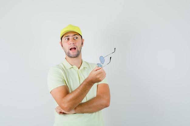 Bezorger in geel uniform met bril en verbaasd, vooraanzicht op zoek.