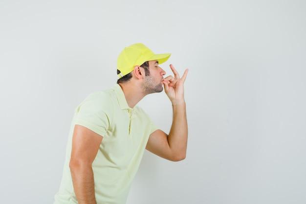 Bezorger in geel uniform met heerlijk gebaar en op zoek verrukt, vooraanzicht.