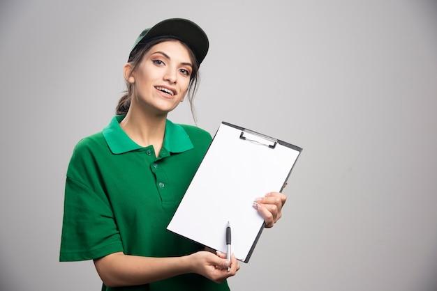 Bezorger in groen uniform laat zien waar ze moet tekenen.