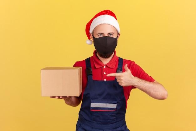 Bezorger in kerstmuts met medisch masker wijzende vinger naar kartonnen doos in zijn hand