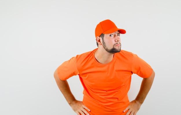 Bezorger in oranje t-shirt die privégesprek afluistert en nieuwsgierig kijkt, vooraanzicht.