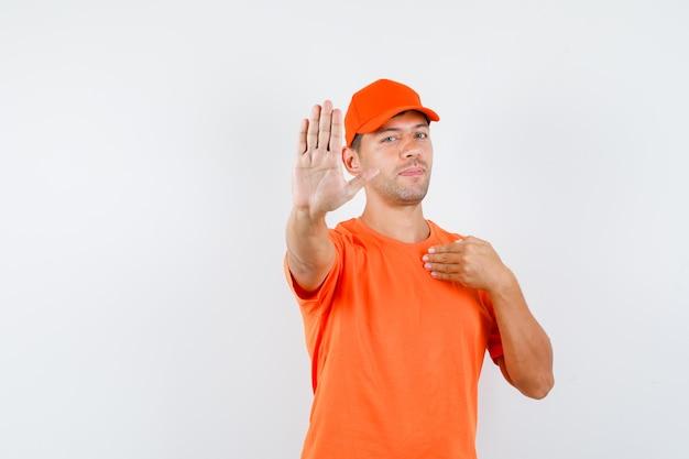 Bezorger in oranje t-shirt en pet met stopgebaar door naar zichzelf te wijzen en zelfverzekerd te kijken