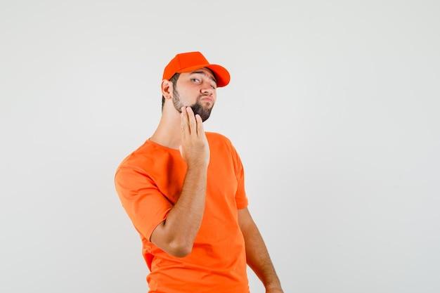 Bezorger in oranje t-shirt, pet die de gezichtshuid onderzoekt door zijn baard aan te raken, vooraanzicht.