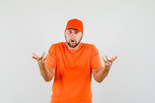 Bezorger in oranje t-shirt, pet die de handen op een vragende manier houdt en verbaasd kijkt, vooraanzicht.