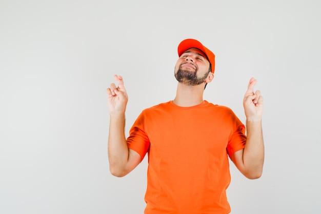 Bezorger in oranje t-shirt, pet die de vingers gekruist houdt en er vredig uitziet, vooraanzicht.