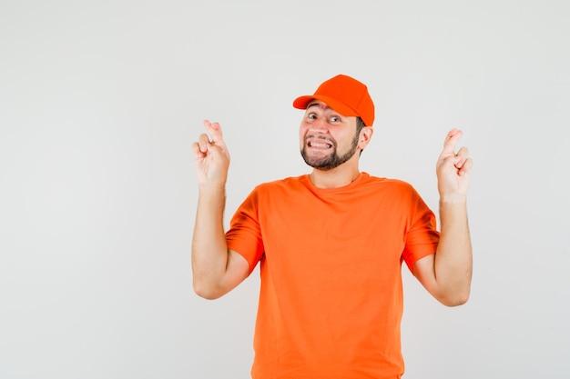 Bezorger in oranje t-shirt, pet die de vingers gekruist houdt en er vrolijk uitziet, vooraanzicht.