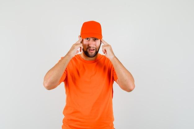 Bezorger in oranje t-shirt, pet die de vingers op de slapen houdt en er verstandig uitziet, vooraanzicht.