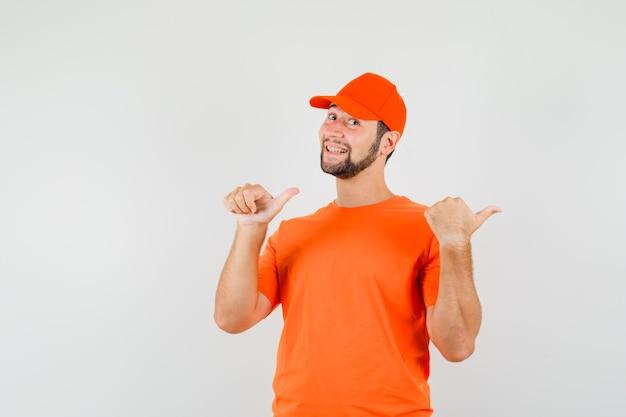 Bezorger in oranje t-shirt, pet die dubbele duimen naar de zijkant wijst en er vrolijk uitziet, vooraanzicht.
