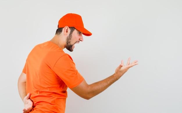 Bezorger in oranje t-shirt, pet die een vraaggebaar maakt en er uitzinnig uitziet.