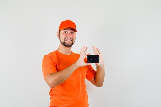 Bezorger in oranje t-shirt, pet die foto maakt op mobiele telefoon en vrolijk kijkt, vooraanzicht.