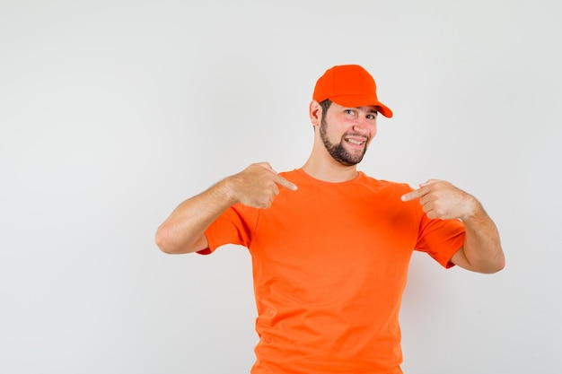 Bezorger in oranje t-shirt, pet die naar zichzelf wijst en er trots uitziet, vooraanzicht.