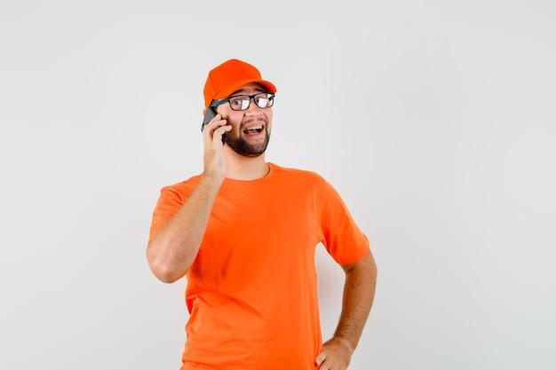 Bezorger in oranje t-shirt, pet die op mobiele telefoon praat en er gelukkig uitziet, vooraanzicht.