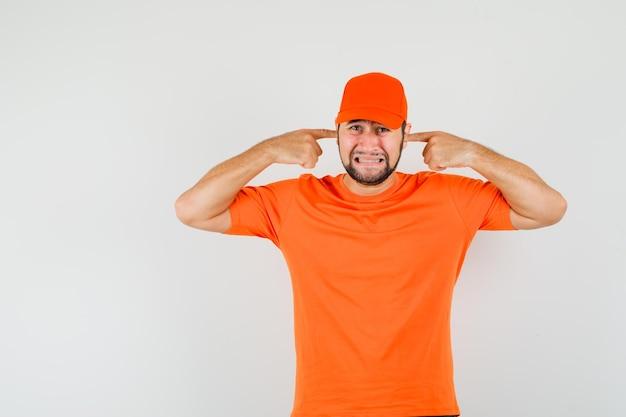 Bezorger in oranje t-shirt, pet die oren stopt met vingers en er geïrriteerd uitziet, vooraanzicht.