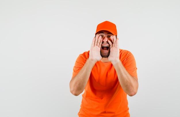 Bezorger in oranje t-shirt, pet die schreeuwt of iets aankondigt, vooraanzicht.
