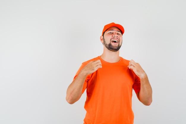 Bezorger in oranje t-shirt, pet die zachtjes aan zijn t-shirt trekt en er trots uitziet, vooraanzicht.
