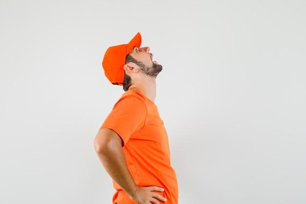 Bezorger in oranje t-shirt, pet die zijn hoofd achterover buigt en er humeurig uitziet.