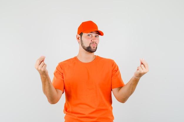 Bezorger in oranje t-shirt, pet gebarend met twee vingers en positief kijkend, vooraanzicht.
