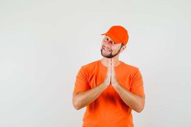 Bezorger in oranje t-shirt, pet hand in hand in biddend gebaar en dankbaar kijkend, vooraanzicht.