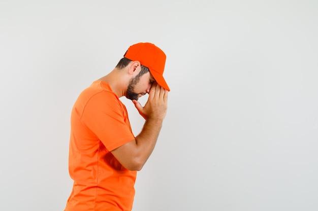 Bezorger in oranje t-shirt, pet hand in hand in biddend gebaar en hoopvol kijkend.