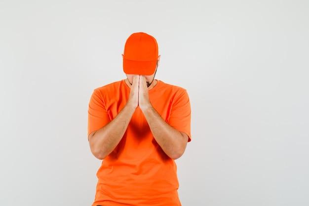 Bezorger in oranje t-shirt, pet hand in hand in biddend gebaar en kalm, vooraanzicht.