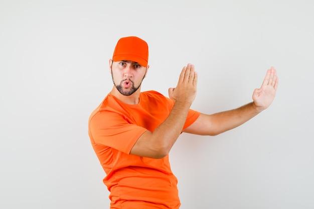 Bezorger in oranje t-shirt, pet met karate chop-gebaar en zelfverzekerd, vooraanzicht.
