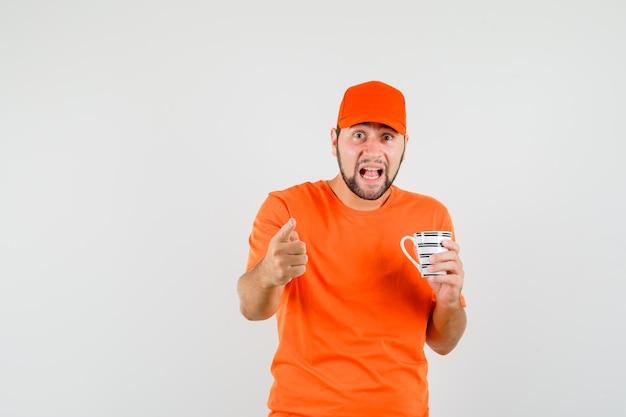 Bezorger in oranje t-shirt, pet met kopje drank, wijzend en verbaasd kijkend, vooraanzicht.