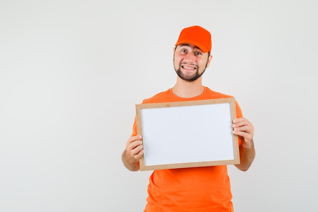 Bezorger in oranje t-shirt, pet met leeg frame en vrolijk, vooraanzicht.