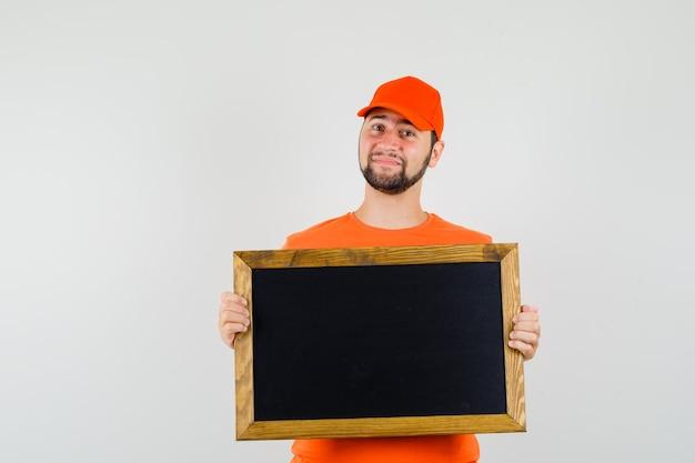Bezorger in oranje t-shirt, pet met leeg schoolbord en zachtaardig, vooraanzicht.