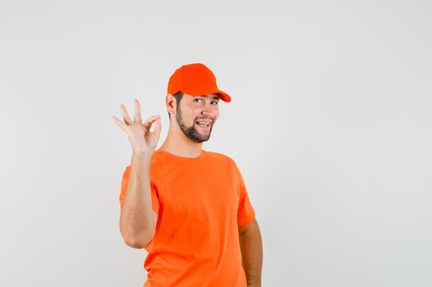 Bezorger in oranje t-shirt, pet met ok gebaar en vrolijk, vooraanzicht.