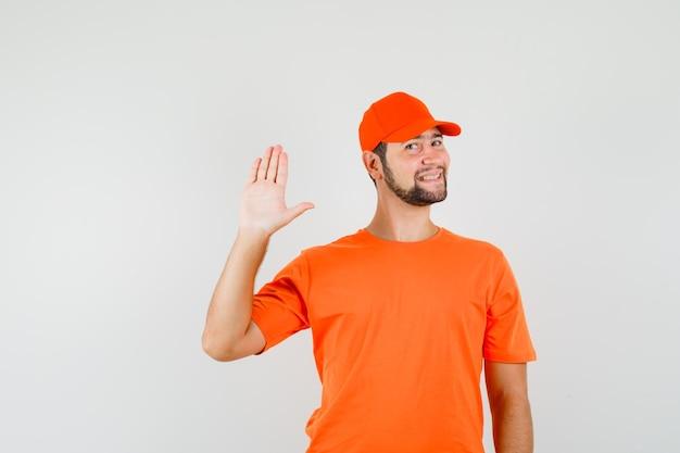 Bezorger in oranje t-shirt, pet met palm en vrolijk, vooraanzicht.