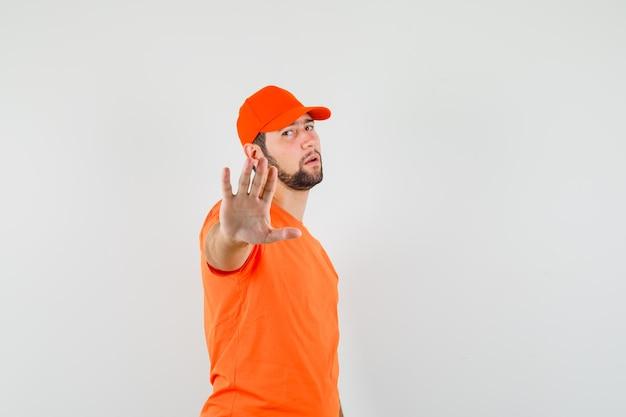 Bezorger in oranje t-shirt, pet met stopgebaar en uitgeput, vooraanzicht.