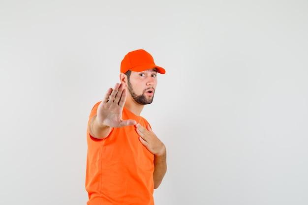 Bezorger in oranje t-shirt, pet met stopgebaar met hand op borst en bang, vooraanzicht.