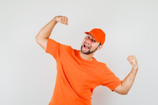 Bezorger in oranje t-shirt, pet met winnaargebaar en zalig, vooraanzicht.