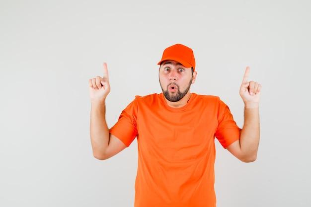 Bezorger in oranje t-shirt, pet naar boven gericht en bang, vooraanzicht.