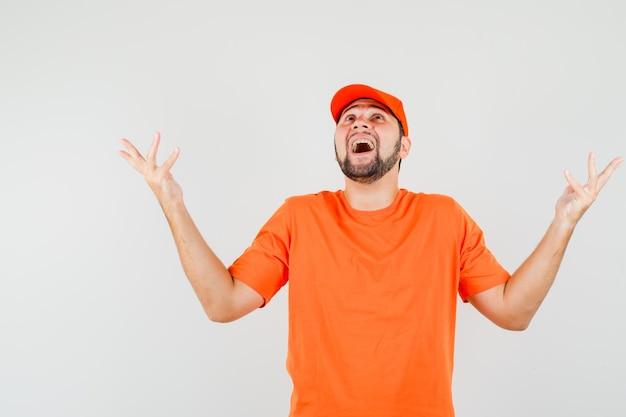 Bezorger in oranje t-shirt, pet opkijkend met opgeheven armen en geluk, vooraanzicht.