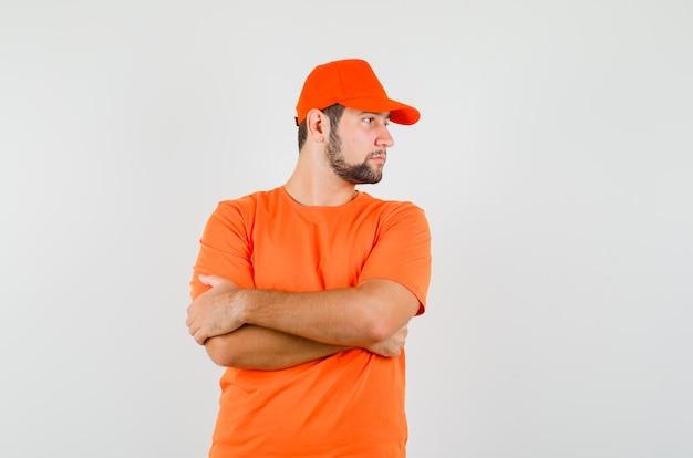 Bezorger in oranje t-shirt, pet opzij kijkend met gekruiste armen en knap, vooraanzicht.