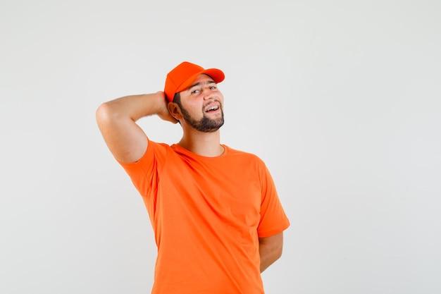 Bezorger in oranje t-shirt, pet poseren met de hand achter het hoofd en zelfverzekerd, vooraanzicht.