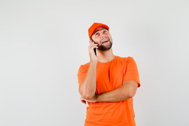Bezorger in oranje t-shirt, pet pratend op mobiele telefoon en vrolijk kijkend, vooraanzicht.