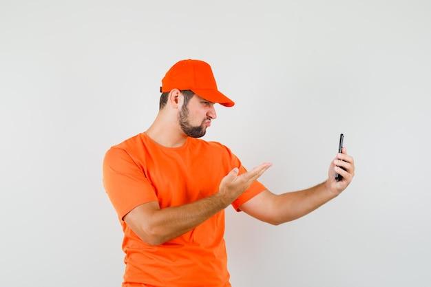 Bezorger in oranje t-shirt, pet pratend op videogesprek en boos kijkend, vooraanzicht.