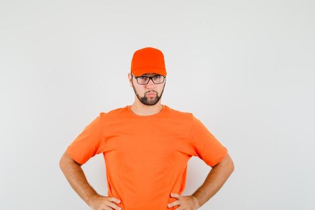 Bezorger in oranje t-shirt, pet staat met handen op taille en ziet er serieus uit, vooraanzicht.