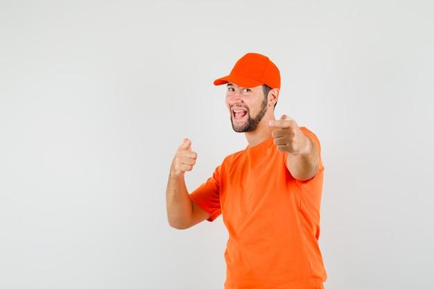 Bezorger in oranje t-shirt, pet wijst en ziet er gelukkig uit, vooraanzicht.